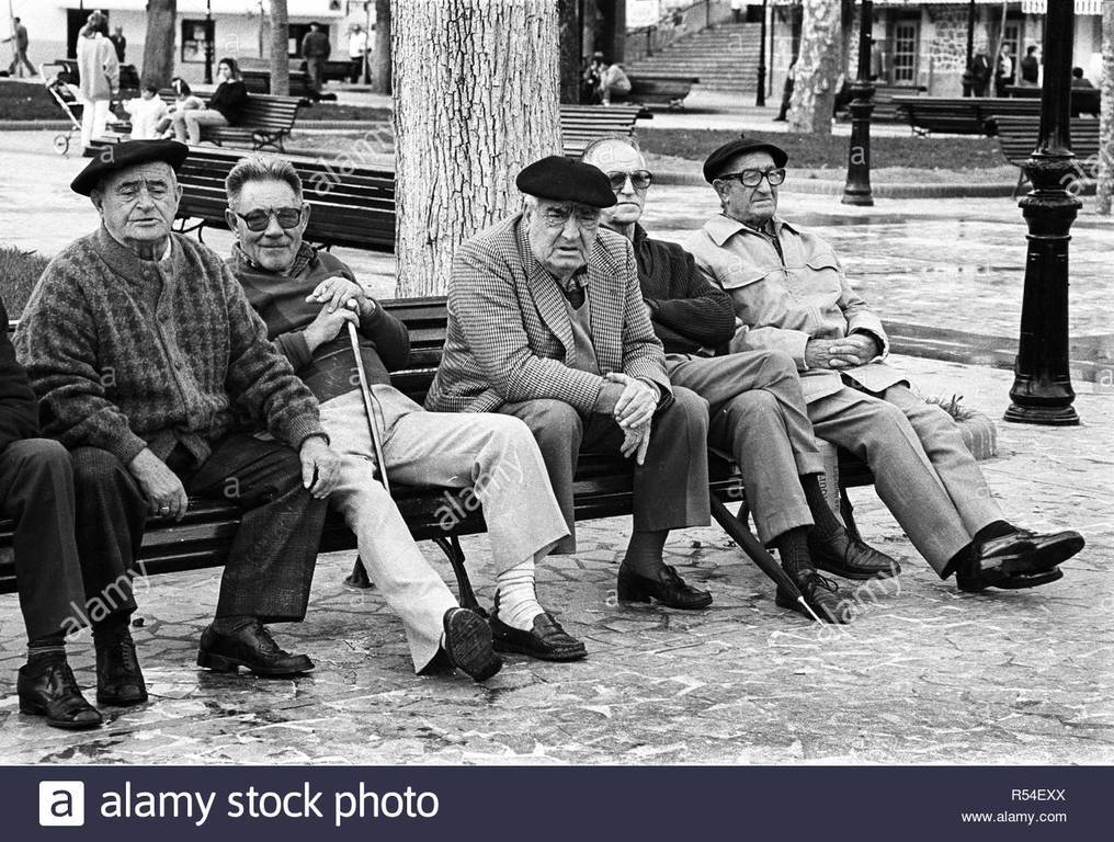 al-basque-berets-sit-on-a-park-bench-in-bermeo-biscay-spain-vintage-black-and-white-image-R54EXX.jpg